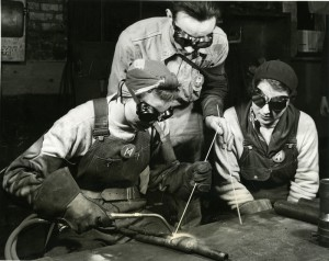 Vintage photo of three people welding steel